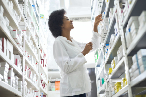 Low angle view of smiling female chemist arranging stock in shelves at pharmacy