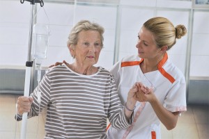 Nurse walking next to a patient with IV drip in hospital